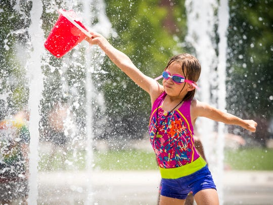 Children play in the fountains at World's Fair Park in downtown Knoxville on Monday, June 18, 2018.