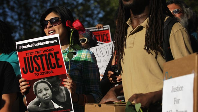 Demonstrators gather in front of the White House on Thursday calling for the Justice Department to fully investigate the Ferguson, Mo., shooting.
