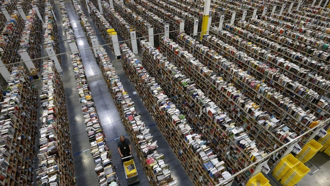 An Amazon employee walks down an aisle at the company's Phoenix warehouse on Dec. 2, 2013. The portion of the retail industry that includes e-commerce has grown tenfold from $35 billion in sales in 1992.