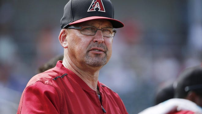 In this file photo from 2015, former Arizona Diamondbacks assistant hitting coach Mark Grace watches the Diamondbacks players during the fourth inning of a spring training baseball game against the Cincinnati Reds Wednesday, April 1, 2015, in Goodyear, Ariz.