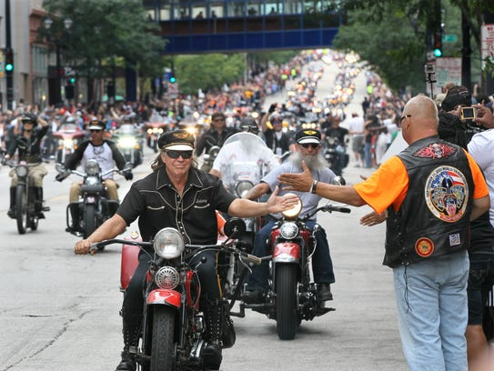 Riders slapped hands as they went past the parade watchers