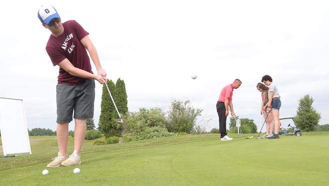 Vance Friend, 15, works on his chipping skills while Tyson  Deskins helps Samantha Fraley and Maddie Seilbel, both 14, with their chipping skills as well at the Oaktree Golf Club.