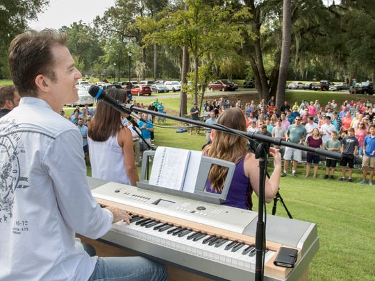 Worship & Creative Arts Pastor Warren Halstrom, left, plays the keyboard as hundreds of worshipers participate during a makeshift outdoor service at Celebration Baptist Church after Hurricane Hermine left them without electricity.