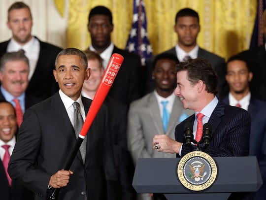Louisville's Rick Pitino hands a bat to then-President Barack Obama in July 2013.