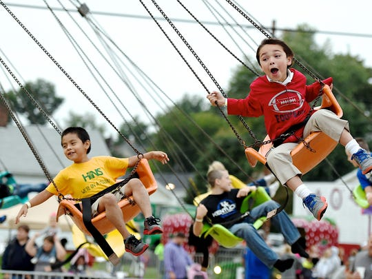 Sam Loeffler, right, enjoys the swings ride at the Holy Name Fall Festival Friday in 2014