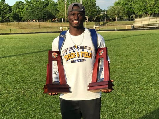 Rickards track coach Johnathan Butler holds district
