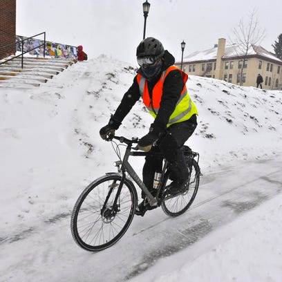 A bundled up cyclist pedals across the University of