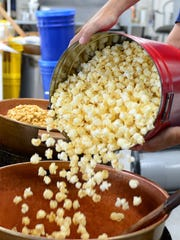 A Fisher's employee mixes the famous caramel popcorn