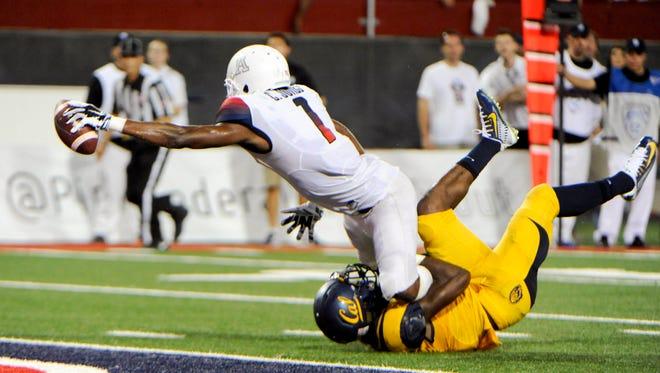 Sep 20, 2014; Tucson, AZ, USA; Arizona Wildcats wide receiver Cayleb Jones (1) scores a touchdown as he is tackled by California Golden Bears cornerback Darius Allensworth (2) during the fourth quarter at Arizona Stadium. Arizona won 49-45.