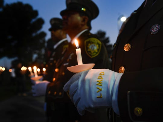 Officer Michael Lemley of the Las Vegas Metro Police Department stands with fellow officers at a candlelight vigil for Charleston Hartfield at Police Memorial Park. Hartfield, an off-duty Las Vegas police officer was killed Sunday during the mass shooting at a music festival across from the Mandalay Bay Hotel and Casino.