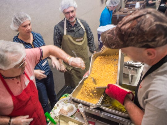 Volunteers gets ready to serve food as Daryl Ewan, right, pours hot corn into a tray on Thanksgiving, Nov. 24, 2016 at the Salvation Army in Chambersburg, Pa.