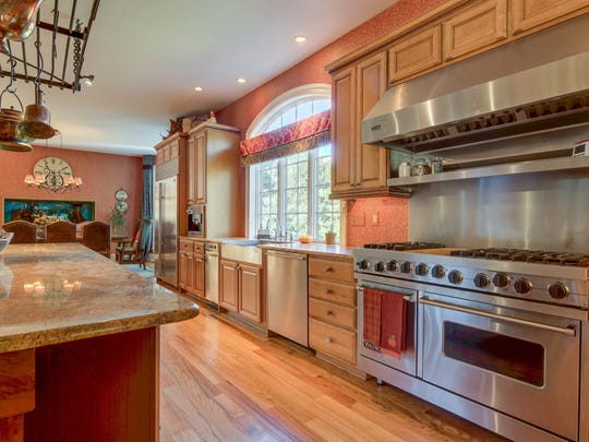 The open-concept kitchen features a large granite-topped island and professional grade appliances, including a temperature-controlled wine cooler.