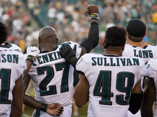 Algunos jugadores como Malcolm Jenkins de las Águilas, alzaron el puño en señal de protesta.