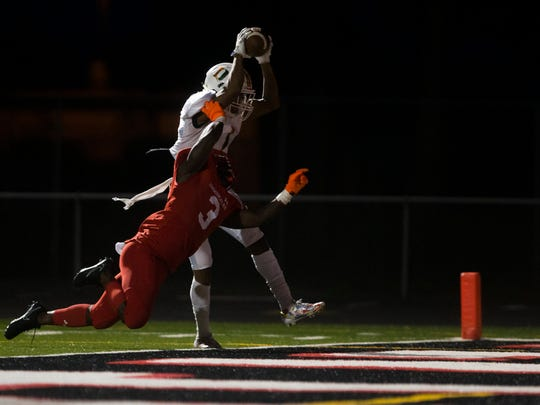 Dunbar's Deven Thompkins (1) hauls in a touchdown grab over Immokalee's Shedro Louis (3) to score the first touchdown of the game in the first quarter of a District 12 matchup Tuesday, October 17, 2017 in Immokalee, Fla.