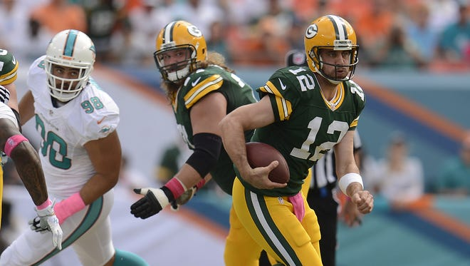 Green Bay Packers quarterback Aaron Rodgers (12) runs with the ball in the first quarter during Sunday's game against the Miami Dolphins at Sun Life Stadium.