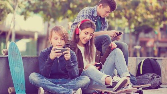 Three teenagers looking at smartphones