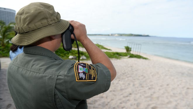 A Guam Department of Agriculture's Division of Aquatics and Wildlife Resources conservation officer peers out towards the ocean from the shoreline of Gun Beach in Tumon on Wednesday, Jan. 13, 2015.