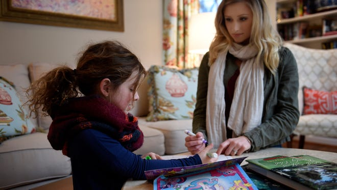 Lucy Hart spends time coloring with baby sitter Jenna Shuffler in Nashville.
