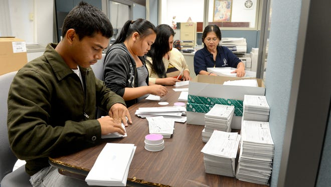 In this file photo, Department of Administration staff  place income tax refund checks in envelopes.
