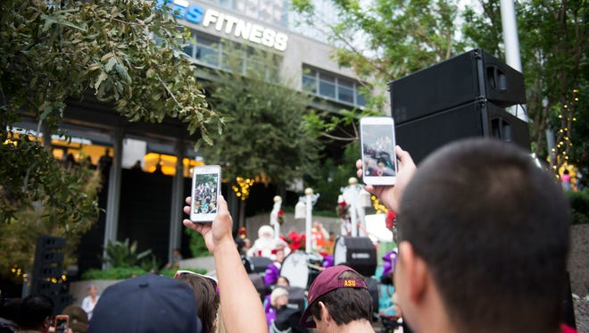 Onlookers take cell-phone videos as the Cesar Chavez High School marching band performs during the grand opening of the CitySkate ice-skating rink at CityScape in downtown Phoenix on Saturday, Nov. 26, 2016.