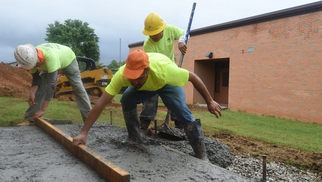 Three construction workers with Tom Davenport Concrete Construction pour a concrete pad outside Flippin Middle School Friday as they work to complete phase three of a construction project. School officials hope to complete phase three by Aug. 14.