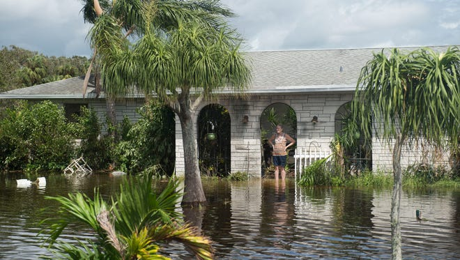 """""""This is enough to shake your faith,"""" said Lon Parsons, of Fort Pierce, after 10 inches of rain flooded his property during Hurricane Irma, seen on Monday, Sept. 11, 2017 on Edwards Road in Fort Pierce. Parsons, his wife Anna Parsons (pictured), and their three dogs rode out the storm as their yard and garage filled with water. """"I swear it was an act of God,"""" Lon Parsons said.""""I just feel blessed that we're not like (Hurricane) Harvey."""""""