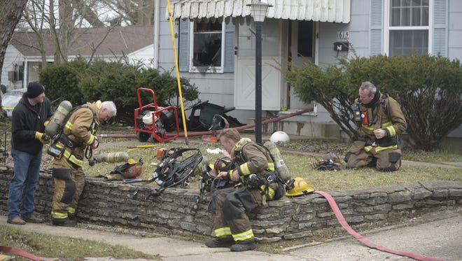 Richmond firefighters rest and remove equipment after fighting a house fire on South West B Street.