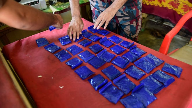 """This photograph taken on April 6, 2018 shows a Bangladesh Border Guard (BGB) laying out small bags of the drug """"yaba"""" recovered from a passenger bus in a search at a checkpost along the Teknaf-Cox's Bazar highway in Teknaf."""