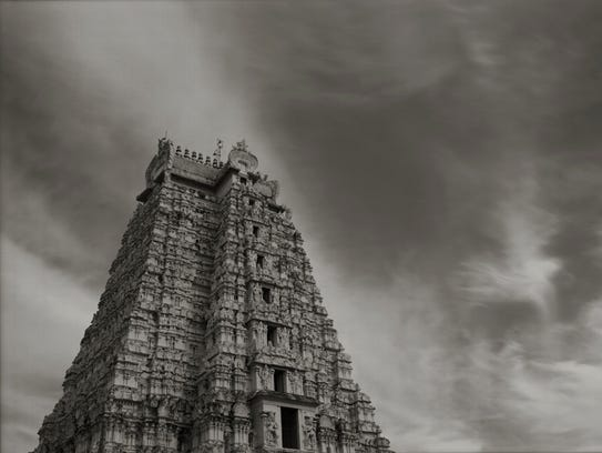 A carved stone temple in Trichi, India, is featured