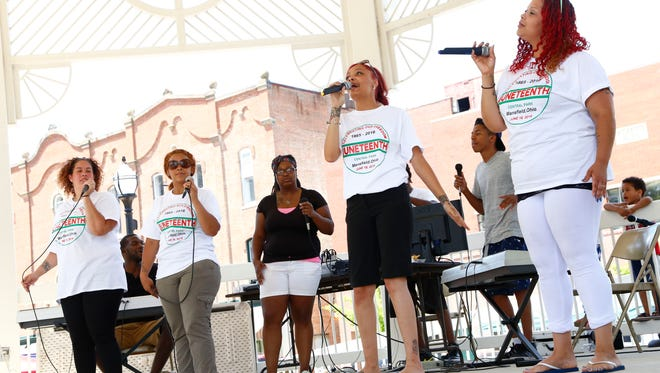 Members of the Power House Worship Center choir sing Saturday in the gazebo at Central Park as part of the Juneteenth celebration.