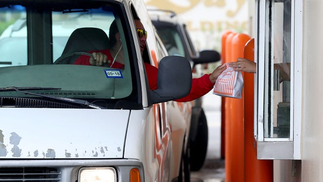 A customer receives his meal after Whataburger by the Bay opens after Hurricane Harvey shut down the business on Sunday, Aug. 27, 2017, in Corpus Christi, Texas.
