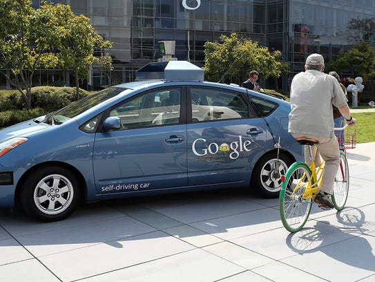A bicyclist rides by a Google self-driving car at the