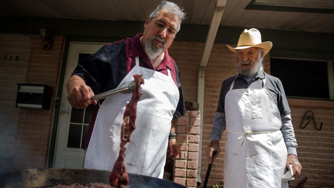 "Juan Antonio ""Sonny"" Falcón, right, and his son John grill skirt steaks for fajitas over a very hot fire. The Kyle City Council drew backlash after announcing that Rebel Drive would be renamed Fajita Drive in memory of Sonny Falcón."