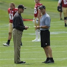 Baltimore Ravens head coach John Harbaugh, right, and San Francisco 49ers head coach Jim Harbaugh talk during a joint football practice, Saturday, Aug. 9, 2014, in Owings Mills, Md.