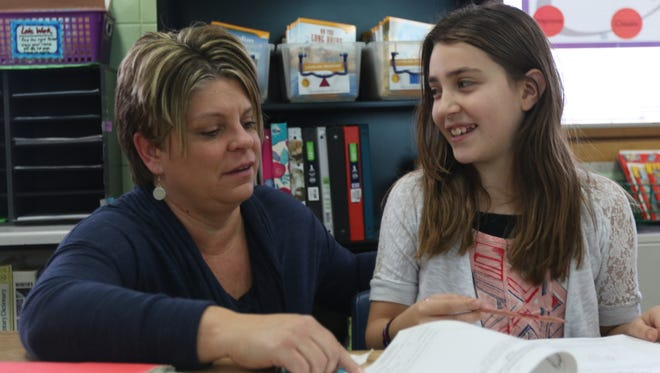 Fifth-grader Alexis Adams, right, smiles at teacher Sara Gawlitta near the end of the school day on Nov. 30, 2016, at Mead Elementary Charter School in Wisconsin Rapids.