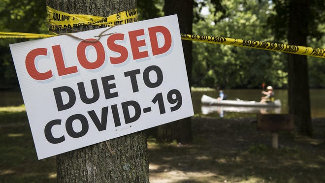 A closed sign and police tape remind visitors that the picnic area at Bordentown City Beach is closed and the beach's daily boat ramp permits are restricted to Bordentown residents only due to COVID-19.
