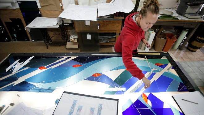 Kristy Meyer, a craftsman at Coventry Glassworks & Gallery, puts a piece of glass designed to mimic rain into place as she cuts pieces for a stained glass window that will be installed at St. Mark's Lutheran Church in Neenah.