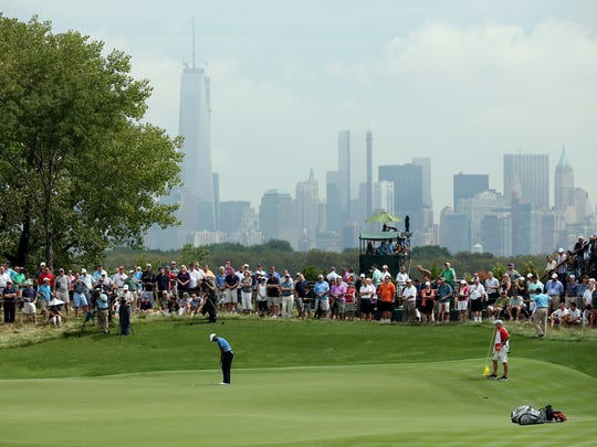 Tiger Woods of the United States putts on the 13th hole during the first round of The Barclays at Liberty National Golf Club on August 22, 2013 in Jersey City.