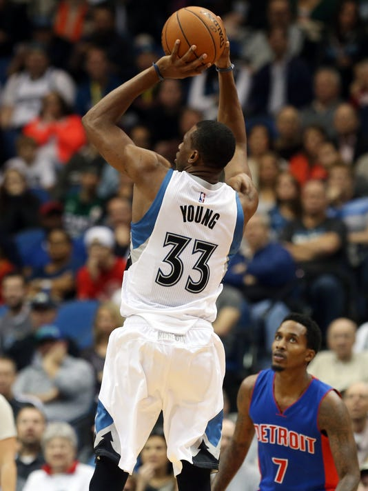 Minnesota Timberwolves'  Thaddeus Young, left, shoots as Detroit Pistons' Brandon Jennings looks on in the second half of an NBA basketball game, Thursday, Oct. 30, 2014, in Minneapolis. The Timberwolves won 97-91. (AP Photo/Jim Mone)