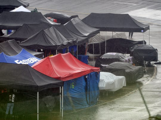 Cars sit under cover as a driving rain falls on the track Sunday during the 49th annual Snowball Derby at Five Flags Speedway.