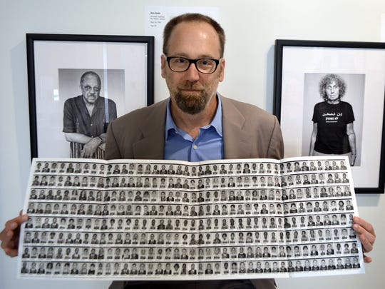 """Eric Etheridge holds a sheet of 328 mug shots of civil rights activists arrested in Mississippi and Alabama. Etheridge was at the Freedom Rides Museum in Montgomery's Historic Greyhound Bus Station on Saturday, Nov. 2, 2013. Etheridge tracked down those arrested during the Freedom Rides of 1961 to photograph them for his book, """"Breach of Peace."""""""