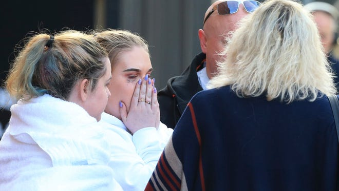 A fan leaves the Park Inn hotel in central Manchester, England, Tuesday, May 23, 2017. Over a dozen people were killed in an explosion following a Ariana Grande concert at the Manchester Arena late Monday evening. (AP Photo/Rui Vieira)