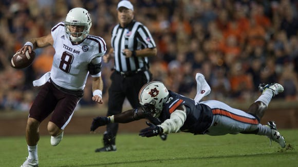 Texas A&M quarterback Trevor Knight (8) runs downfield as Auburn linebacker Tre' Williams (30) attempts to tackle him during the Auburn vs. Texas A&M NCAA football game on Saturday, Sept. 17, 2016, at Jordan Hare Stadium in Auburn, Ala.  