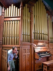 Dan Cook crawls out from behind the inner workings of a 1905 George Kilgen & Son pipe organ that's at the now-closed West Nashville United Methodist Church in Nashville. He wants to get rid of the organ but not send it to a landfill.