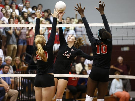 Chiles' Aly Freelancd spikes the ball as Leon's Kate Carter, left, and Makayla Washington defend during their match at Chiles High School on Thursday.