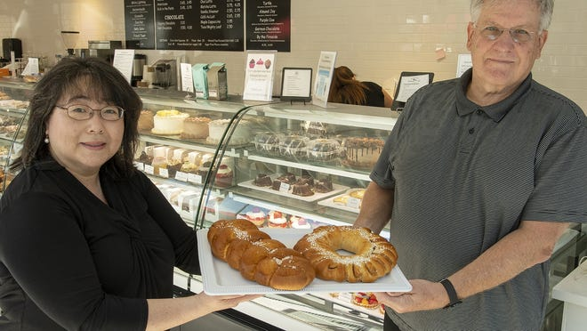 Bean Counter Bakery Cafe owner Alice Lombardi holds Swedish coffee bread with Crown Bakery owner Jon Lundstro.