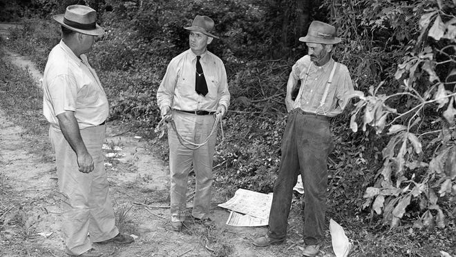 Loy Harrison, left, shows Sheriff J.M. Bond, center, of Oconee County, and Coroner W.T. Brown, of Walton County, where four African-Americans were slain by a mob of white men on July 25, 1946, in Monroe, Georgia. Harrison said the mob took the African-Americans, two men and two women, from his car and carried them into the woods where they were shot. Bond holds the rope which the mob used to bind the hands of the two men together.