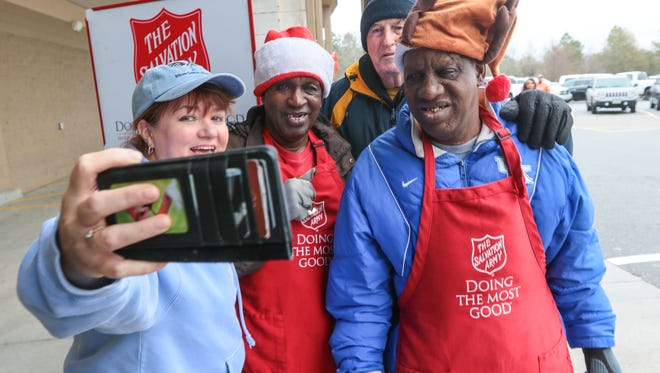 "Hope Harrison, left, of Anderson gets a selfie photo with George ""Cool Rock"" Kennedy, Harold Jones, and James Robert ""Radio"" Kennedy of Anderson at a Salvation Army Red Kettle on Saturday at the Sam's Club in Anderson."