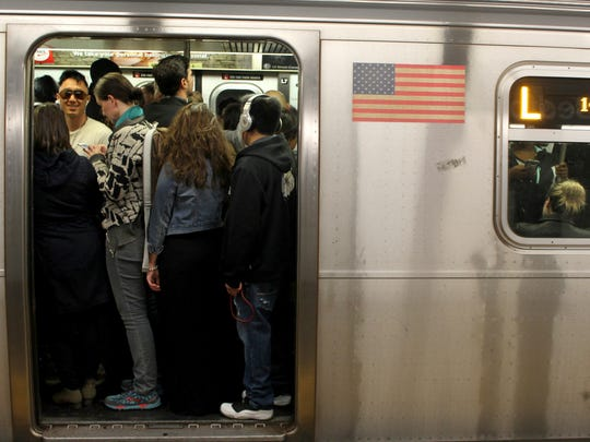 FILE - This May 5, 2016 file photo shows passengers crowd on the L Train subway in the Brooklyn borough of New York. Tourists who decide to try the subways will find them crowded, noisy and confusing, but they are the most efficient way to get around the city.