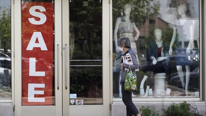 A woman wearing a mask walks past a retail store in Deerfield on Thursday. On Friday, the number of COVID-19 cases reported in a 24-hour period in Illinois fell below 600 for the first time since March 30.